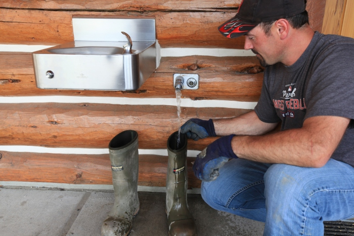 Ryan fills up his boots with water to transfer to the coolant reservoir on his truck at the Lolo Pass Visitor Center on the MT-ID border.